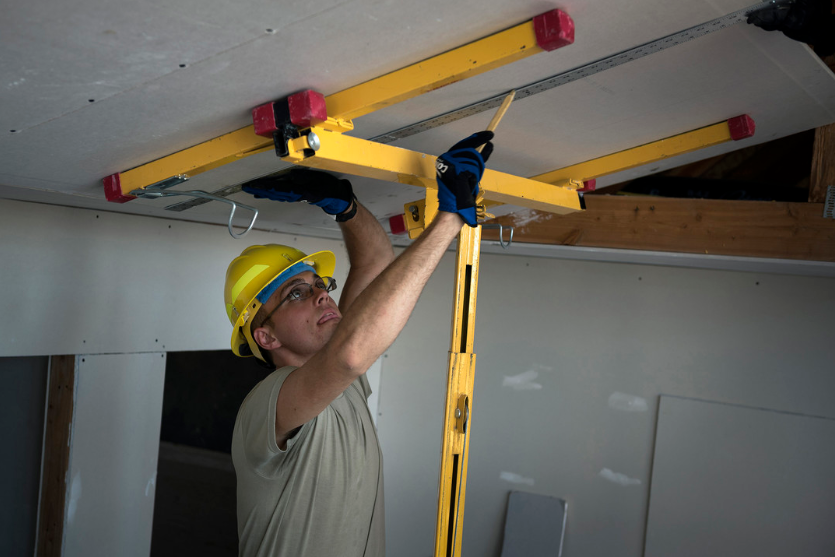 this image shows a man doing a project for stretch ceiling in houston